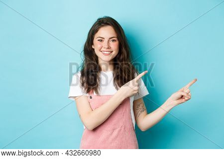 Image Of Cute Teenage Girl Smiling, Pointing Fingers Right At Promo Offer, Demonstrating Banner On C