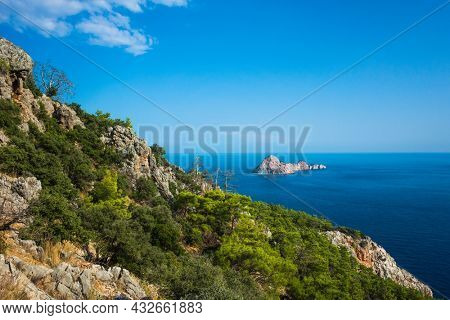 Island Suluada near Turkish coast of Mediterranean sea view from steep mountain, deep blue sea water, sunny day, Picturesque nature of Antalya province, Turkey