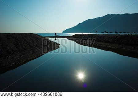 Man is fishing where small river flows into the sea, High contrast silhouette photo against sun, Sun reflecting in water, Parasols on the beach, Adrasan beach on Mediterranean sea in Turkey