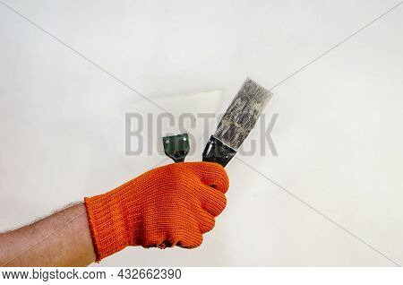 A Hand In A Red Protective Glove Holds Two Trowels Against The Wall. A Man With A Hand-held Wall Put