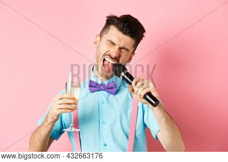 Party And Festive Events Concept. Drunk Funny Guy Singing In Microphone And Drinking Champagne From