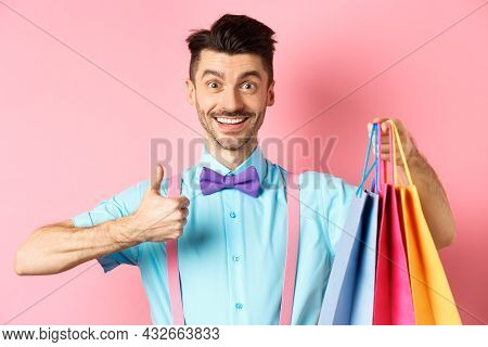 Happy Male Shopper Showing Thumbs Up And Shopping Bags, Recommending Store, Standing On Pink Backgro