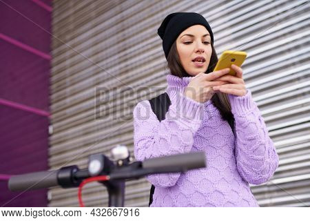 Woman In Her Twenties With Electric Scooter Recording Voice Note With A Smartphone Outdoors.