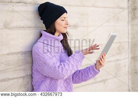 Female Student In Her Twenties Using Digital Tablet Outdoors.