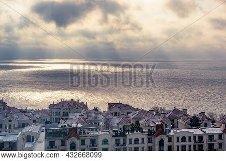 View Of Houses And Rooftops Against The Backdrop Of The Sea In Cloudy Weather, The Sun's Rays Make T
