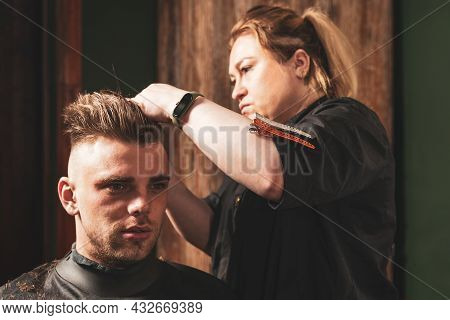 Girl Hairdresser Doing Hairstyle And Styling With Scissors And Comb To A Young Man.