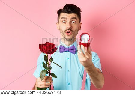 Valentines Day. Funny Man With Moustache And Bow-tie Making Proposal, Showing Engagement Ring And Pr