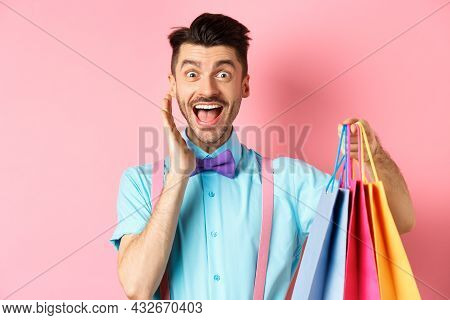Surprised And Happy Man Screaming Of Joy And Holding Shopping Bags, Shopper Seeing Discounts, Standi
