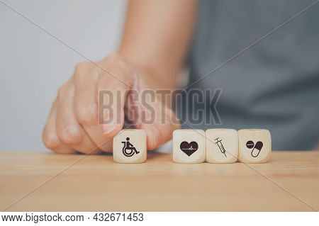 Senior Human's Hand Holding Disabled Person Icon And Other Health And Medical Sign On Wood For Healt