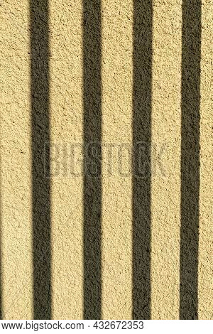 Brown Background Of Fine Plaster Outdoors In Sun. With Shadows From Grate Or Fence. Close-up.