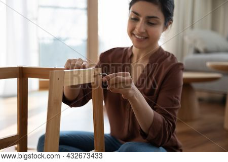 Happy Young Indian Woman Enjoy Easy Mounting Flat Pack Furniture