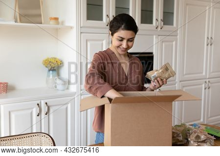 Satisfied Young Indian Woman Unpack Box With Groceries Ordered Online