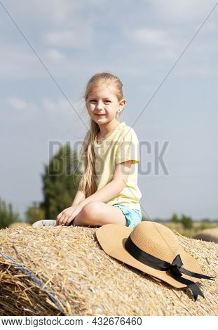 Little Girl Having Fun In A Wheat Field On A Summer Day. Child Playing At Hay Bale Field During Harv