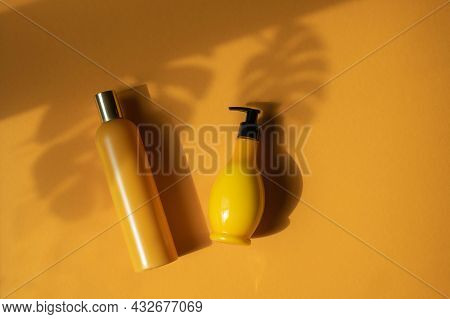 Mockup Of Yellow Cosmetic Bottles With Shadow Monstera Leaves On Yellow Background. A Creative, Mini
