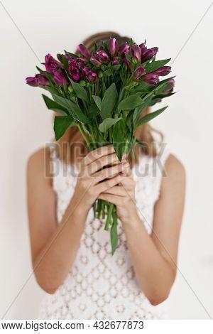 Alstroemeria Flowers. Faceless Portrait With Fresh Purple Flowers. Woman In White Dress Holding A Bo