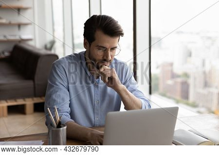 Pensive Young Caucasian Male Employee Work On Computer