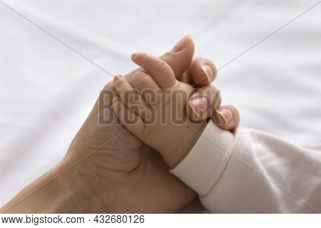 Young Mom Touching Little Palm Of Little Baby