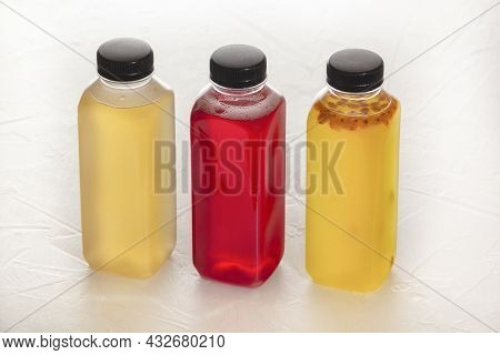 Three Plastic Bottles With Fruit Fruit Drinks In Red And Yellow Stand On A White Table