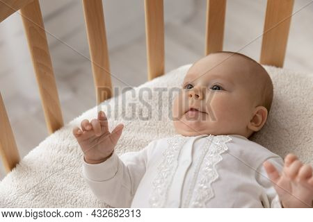 Smiling Little Cute Few Month Baby Lying In Crib