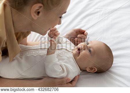 Happy New Mom Cuddling, Hugging Cute Lying Baby