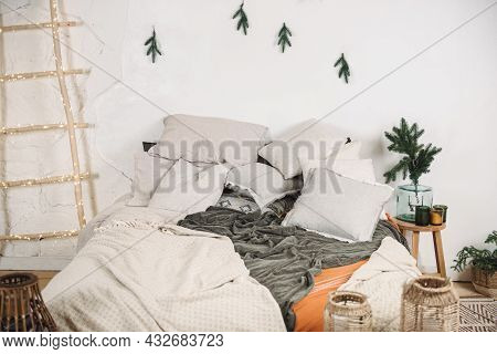 Modern Christmas Interior Of Bedroom: Bed With Pillows And A Blanket, Branches Of A Christmas Tree,