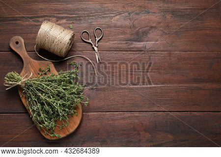 Bunch Of Aromatic Thyme, Scissors And Twine On Wooden Table, Flat Lay. Space For Text