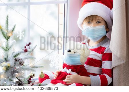 Happy Child Wearing Christmas Pajamas Sitting On Windowsill