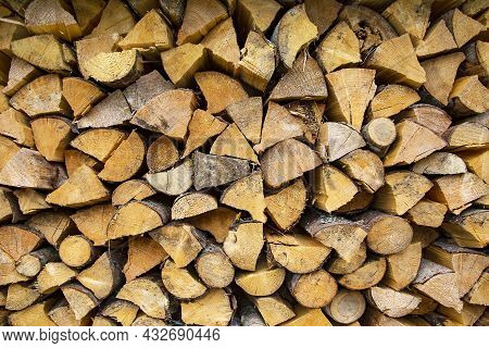Firewood Background Of Chopped Wood For Kindling And Heating The House Close Up. Woodpile With Stack