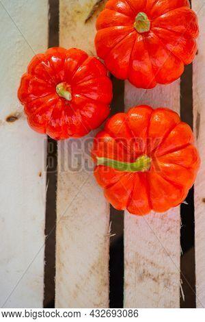 Small Orange Pumpkins On A Wooden Background Lie