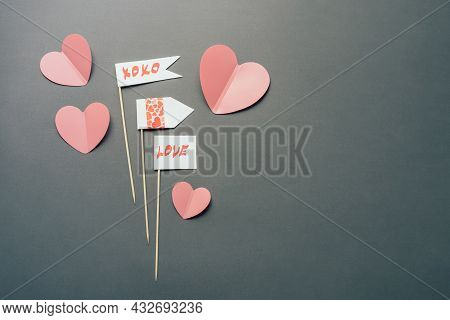 On The Gray Background Lie Valentine Props With Romantic Messages And Pink Paper Hearts And Copy Spa