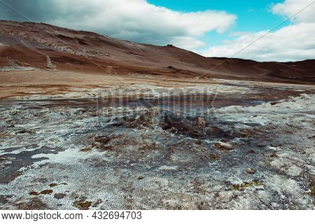 Mudpots In The Geothermal Area Hverir, Iceland. The Area Around The Boiling Mud Is Multicolored And