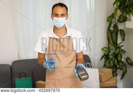 Last Step Of The Shopping Is Payment. A Man Holding A Card Cash Register. Credit Card Reader