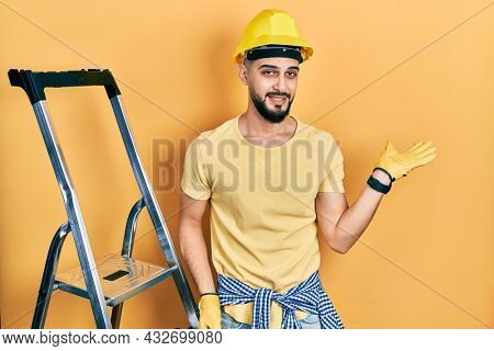 Handsome man with beard by construction stairs wearing hardhat smiling cheerful presenting and pointing with palm of hand looking at the camera.