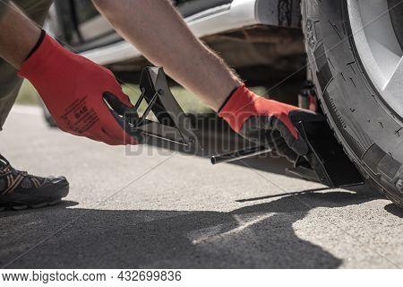 Hands Putting Wheel Chocks Under Car Tyre On Road, Bottom View.