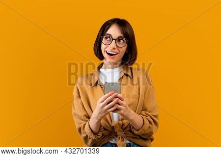 Dreamy Young Woman Using Smartphone And Looking Aside, Standing Over Yellow Studio Background