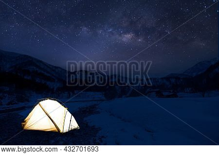 Camping In The Wilderness. A Pitched Tent Under The Glowing Night Sky Stars Of The Milky Way With Sn