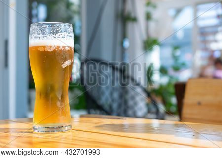 Beer In A Glass On A Brown Table With A Blurry Background