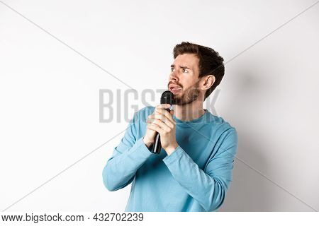 Worried And Confused Man Reading Lyrics On Karaoke, Looking Left With Unsure Face, Holding Microphon
