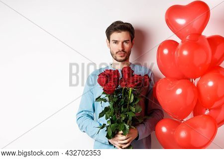 Valentines Day Romance. Confident Young Man Holding Bouquet Of Red Roses, Standing Near Hearts Ballo