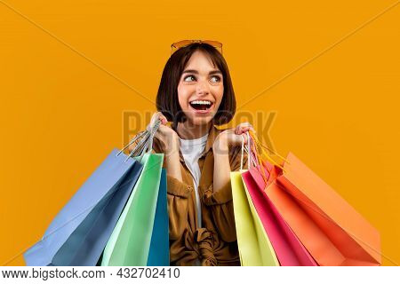 Shopaholic And Seasonal Sales Concept. Excited Woman Holding Lot Of Bright Shopping Bags And Looking