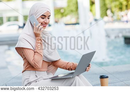 Happy Millennial Arab Islamic Female In Hijab Digital Nomad Calls On Smartphone