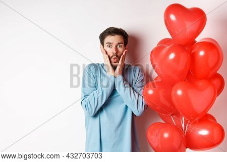 Valentines Day. Image Of Young Man Standing Near Hearts Balloons With Shocked Face, Staring Startled