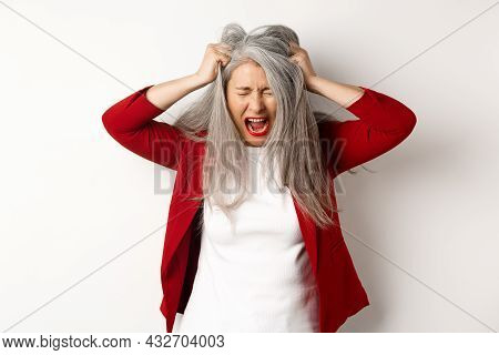 Distressed And Pissed-off Asian Senior Woman Pulling Hair And Screaming, Standing Upset Over White B