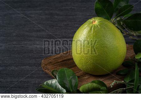Fresh Pomelo Fruit On Black Slate Background.