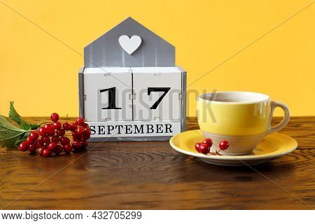 Calendar For September 17 : The Name Of The Month In English, Cubes With The Number 17, A Yellow Cup