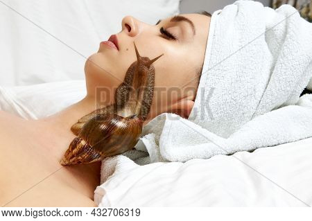 Beautiful Young Woman With A Snail On Her Face Lying On A White Bed, Cosmetic Procedure.