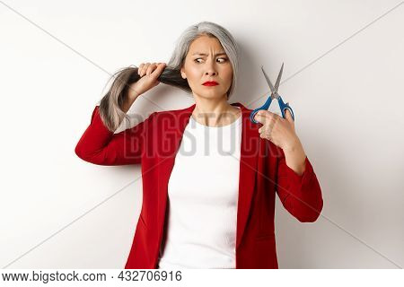 Indecisive Asian Woman Holding Scissors And Looking Doubtful, Thinking To Cut Hair, Changing Haircut