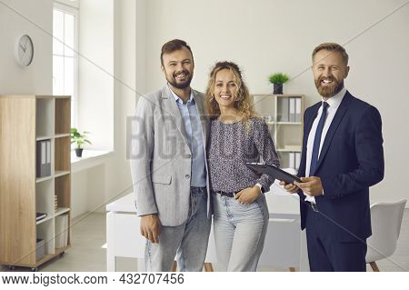 Happy Clients Together With Real Estate Agent Or Mortgage Broker Standing In Office And Smiling