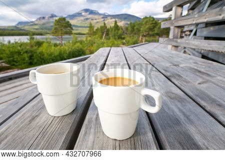 Two White Cups Filled With Coffee With Milk On A Wooden Table With Arctic Landscape Of Swedish Lapla