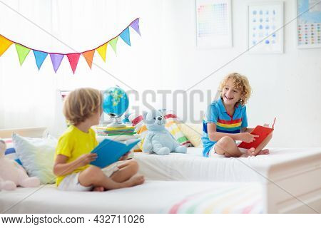 Child Reading Book In Bed. Bedroom For Two Kids. Little Boys Read Books On White Bed With Colorful B